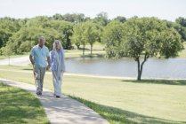 Senior couple walking on path in park by lake. — Stock Photo
