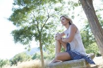 Mid adult woman sitting among park trees. — Stock Photo