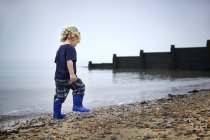 Boy in rubber boots walking on sandy beach. — Stock Photo