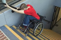 Young man with spinal cord injury in wheelchair going down subway stairs backwards. — Stock Photo
