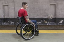 Young man with piercing in wheelchair waiting on subway platform. — Stock Photo
