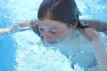 Preteen fille avec taches de rousseur nager dans la piscine. — Photo de stock