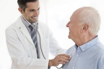 Männlichen Arzt untersuchen ältere Patienten mit Stethoskop — Stockfoto