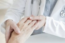 Ärztin hält ältere Patientin an der Hand. — Stockfoto
