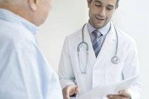 Arzt hält medizinische Notizen und spricht mit Seniorin. — Stockfoto