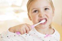 Elementary age girl brushing teeth. — Stock Photo