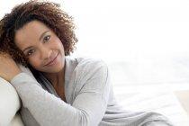 Красивая женщина, улыбаясь сидя в помещении — стоковое фото