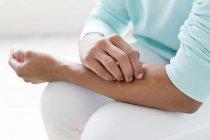 Женщина царапает руку — стоковое фото