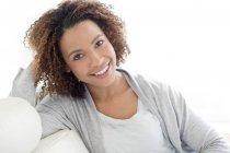 Красива жінка, посміхаючись, сидячи в приміщенні — стокове фото