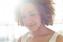 Жінка посміхаючись і, дивлячись — стокове фото