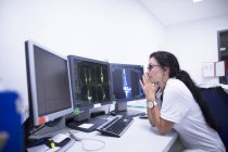 Female radiologist studying CT scans on monitors. — Stock Photo