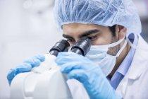 Homme scientifique portant une casquette chirurgicale en utilisant un microscope . — Photo de stock