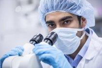 Scientifique masculin en casquette chirurgicale au microscope . — Photo de stock