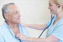 Doctora examinando paciente con estetoscopio . - foto de stock