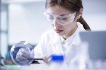 Assistante de laboratoire féminine utilisant l'équipement . — Photo de stock