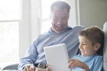 Großvater und Enkel mit digital-Tablette und lächelnd im Innenbereich — Stockfoto