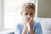 Preteen boy blowing nose indoors. — Stock Photo