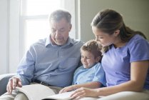 Grandfather, mother and son reading book together. — Stock Photo