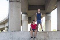 Atletas masculinos descansando sob ponte de concreto . — Fotografia de Stock