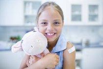 Portrait of girl with plaster on shoulder hugging teddy bear. — Stock Photo