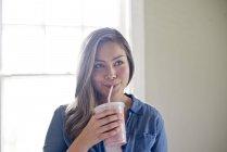 Jeune femme buvant milkshake à la consommation de paille — Photo de stock