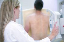 Female doctor examining male chest with x-ray. — Stock Photo