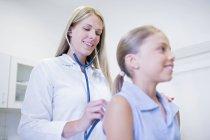 Médico femenino examinando a una joven con estetoscopio . - foto de stock