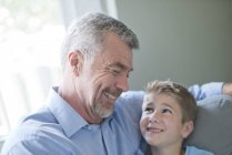 Дедушка и внук сидят лицом к лицу и улыбаются. . — стоковое фото