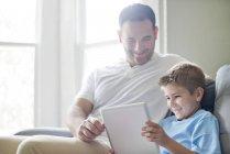 Padre e hijo usando tableta digital en el sofá . - foto de stock