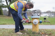 Water department technician opening fire hydrant to flushing water. — Stock Photo