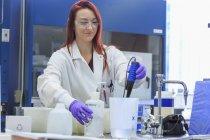 Chemikerin fügt destilliertes Wasser hinzu, während sie ph misst. — Stockfoto