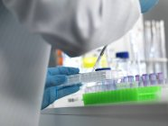 Scientist pipetting samples into multi well plate for automated testing in laboratory. — Stock Photo