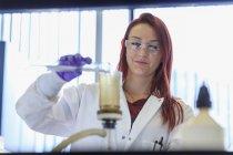 Weiblichen Chemiker Filtration Sieb Probe hinzufügen — Stockfoto