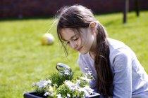 Предрожденная девочка рассматривает цветы с увеличительным стеклом . — стоковое фото