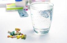 Divers médicaments et verre d'eau sur table. — Photo de stock