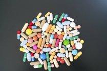 Multicolor de píldoras y cápsulas sobre fondo negro. - foto de stock