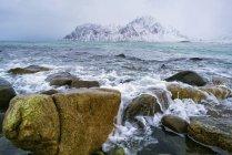 Скелястому узбережжі засніжені гори в відстань. — стокове фото