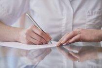 Обрезанный вид женского остеопата, делающего заметки . — стоковое фото