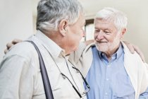Two senior men in care home looking at each other and embracing. — Stock Photo
