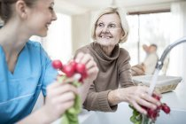Female care worker washing radishes with senior woman in care home. — Stock Photo