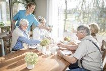 Operaio di cura femminile che serve adulti senior a tavola in casa di cura. — Foto stock