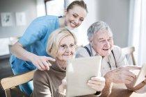 Infirmière souriante aidant le couple âgé à utiliser des tablettes dans la maison de soins . — Photo de stock
