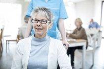 Senior femenino sonriendo y mirando en la cámara con la enfermera en el cuidado de hogar. - foto de stock