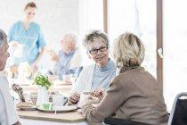 Senior women talking at breakfast in care home. — Stock Photo