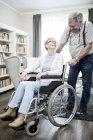 Femme âgée en fauteuil roulant regardant l'homme âgé et souriant . — Photo de stock