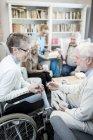 Старшая женщина в инвалидной коляске разговаривает с другом-мужчиной в гостиной дома престарелых . — стоковое фото