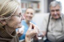 Donna anziana che prende la pillola in casa di cura mentre l'infermiera e l'uomo anziano guardando . — Foto stock