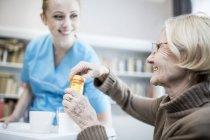 Female nurse smiling and holding tray while senior woman opening medicine bottle. — Stock Photo
