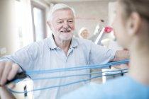 Senior woman mit Widerstand Band in Übung mit Arbeiter — Stockfoto