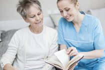 Cheerful nurse reading book with senior woman in care home. — Stock Photo